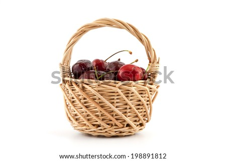 Basket with red ripe cherries on a white background