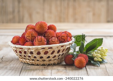 Basket with ripe arbutus unedo fruits, leaves and floers on a wooden background - stock photo