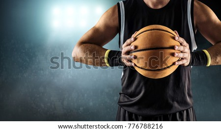 Basketball ball in a male hands, player in black with orange sport ball.