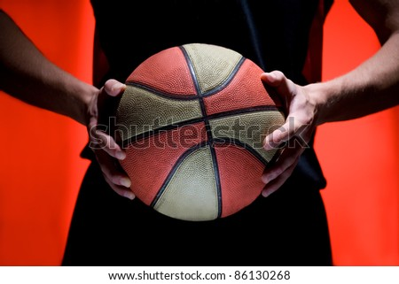 Basketball ball in hands of player isolated red background - stock photo