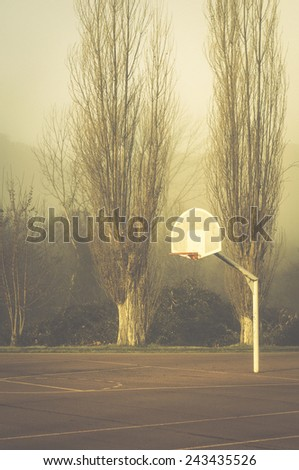 Basketball court and trees outside in a foggy morning - stock photo
