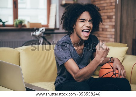 Basketball fan. Cheerful young African man watching TV and holding basketball ball while gesturing on the couch at home - stock photo