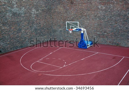 Basketball hoop and an empty outdoor court. - stock photo