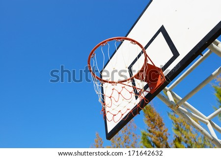 Basketball hoop and modern backboard with blue sky - stock photo