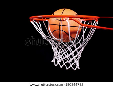 Basketball in hoop on black background - stock photo