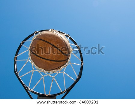Basketball in net against blue skies - successful end to hard work - abstract concept of reaching one's goals, with copy space - stock photo