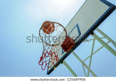 Basketball in the basket on blue sky in summer. - stock photo