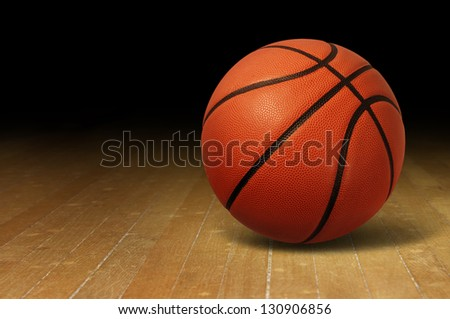 Basketball on a hardwood court floor as a sports and fitness symbol of a team leisure activity playing with a leather ball dribbling and passing in competition tournaments. - stock photo