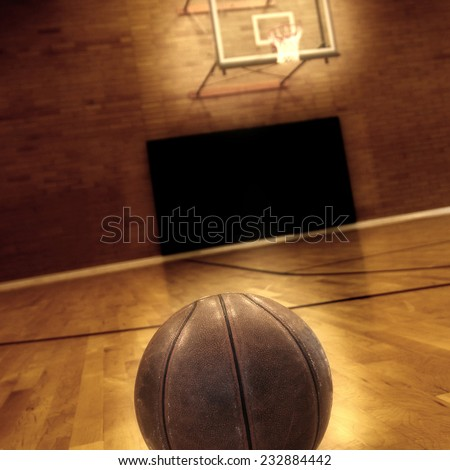 Basketball on floor of empty basketball court - stock photo