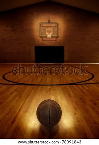 Basketball on floor of empty basketball court - stock photo
