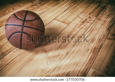 Basketball on Hardwood 3. A basketball laying on the ground of a hardwood court in a gymnasium. - stock photo