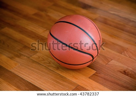 Basketball on the hardwood basketball floor in a stadium - stock photo