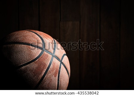 Basketball on wood background with copy-space and dark tone.