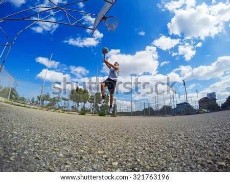 basketball player driving to the basket in a playground on a cloudy day - stock photo