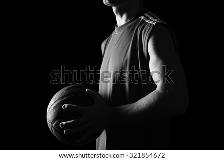 Basketball player holding ball isolated on black background