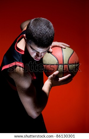 Basketball player holding ball isolated on red background - stock photo