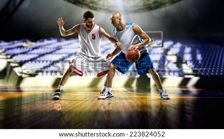Basketball player in action on empty stadium - stock photo