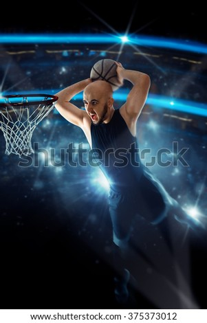 Basketball player in black jersey makes a slam dunk in the game.  Basketball game. Sportsman plays basketball. - stock photo