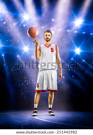 Basketball player is spinning ball on the finger in gym - stock photo