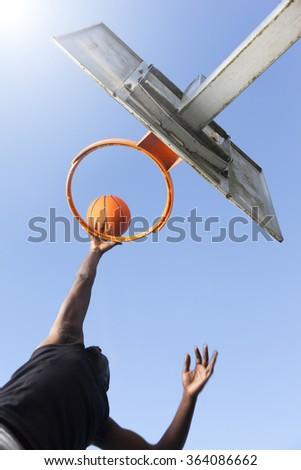 Basketball player jumping to dunk - stock photo