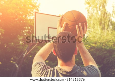 Basketball player on a outdoor court. - stock photo