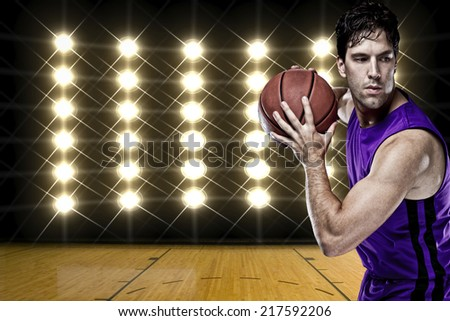 Basketball player on a  purple uniform, in front of lights. - stock photo