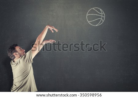 Basketball player shooting a drawn ball on the chalkboard - stock photo