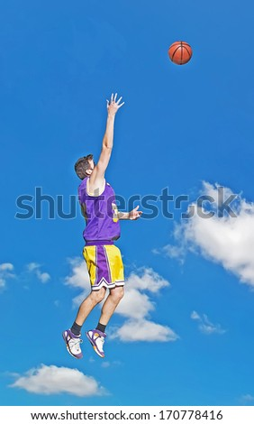basketball player shooting with the sky in the background