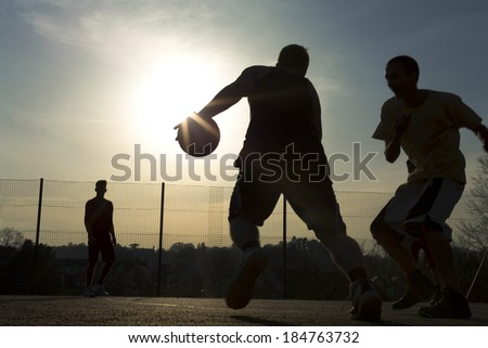 Basketball player silhouettes playing on an outdoor court as the sun creates a flare by the ball - stock photo
