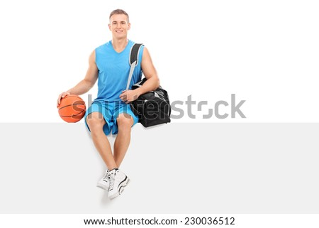 Basketball player sitting on a blank panel isolated on white background - stock photo