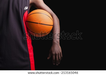 Basketball player standing with a basket ball on black background - stock photo