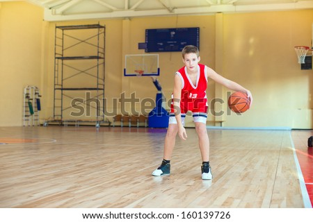 Basketball player with a ball in his hands and a red uniform.  Basketball player practicing in the gym - stock photo