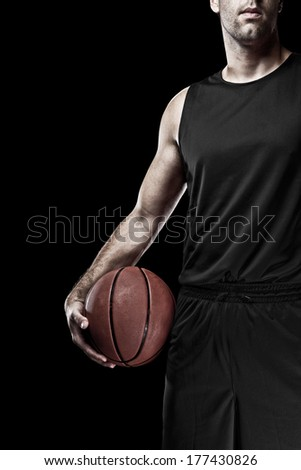 Basketball player with a Black uniform on a black background. - stock photo
