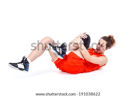 Basketball player with an expression of severe pain in his leg. - stock photo