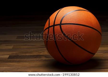 Basketball sitting on hardwood floor in spotlight. - stock photo