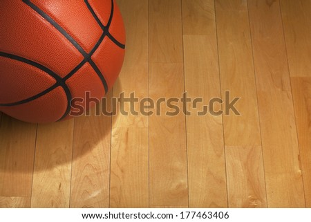 Basketball with spot lighting on a wood gym floor - stock photo