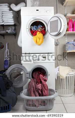 Baskets of dirty laundry in the washing room with dryer and washing machine - stock photo