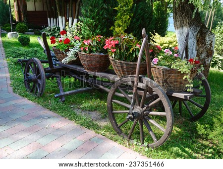 Baskets of flowers on ancient peasant cart on a sunny day