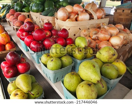 Baskets of freshly harvested green pears, red apples, golden yellow onions and more are for sale at a roadside produce stand.