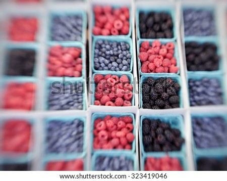 Baskets of raspberries, blueberries, blackberries and strawberries on display in a market. The colors contrast in an alternating pattern. (Note: photo is blurred intentionally with a LensBaby lens.) - stock photo