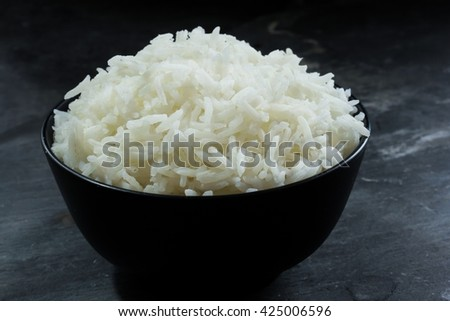 Basmati rice bowl, Cooked basmati rice in a black bowl on dark moody background, selective focus - stock photo