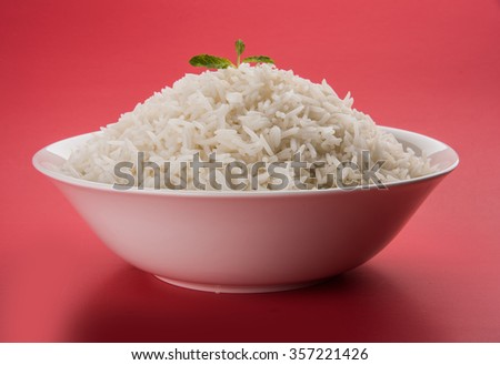 basmati rice in a brass bowl, cooked basmati rice, cooked plain rice, cooked white basmati rice, steamed basmati rice served in white bowl over colourful background - stock photo
