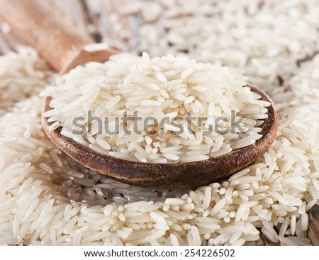 Basmati rice in  a wooden  spoon . Selective focus - stock photo