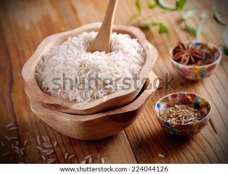 Basmati rice in wooden bowl with other ingredients around - stock photo