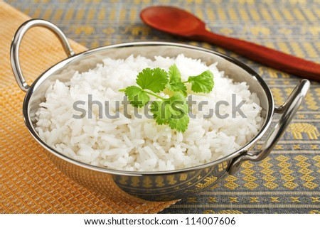 Basmati rice, perfectly cooked, in a steel karahi with a garnish or coriander. - stock photo