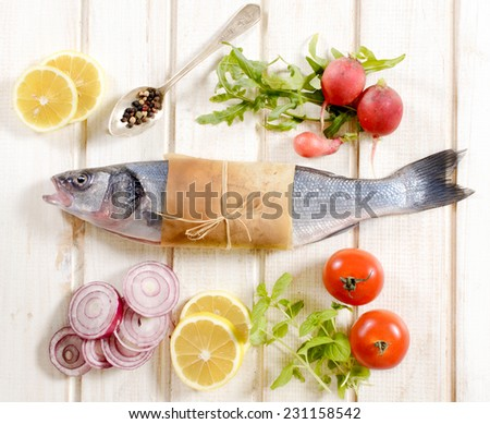 Bass fish from above on the white wooden background  - stock photo