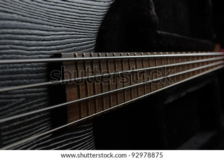 Bass guitar neck on the black background - stock photo
