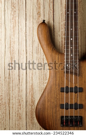 bass guitar on aged wood background - stock photo