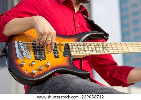 Bass guitar player in dress clothes - stock photo