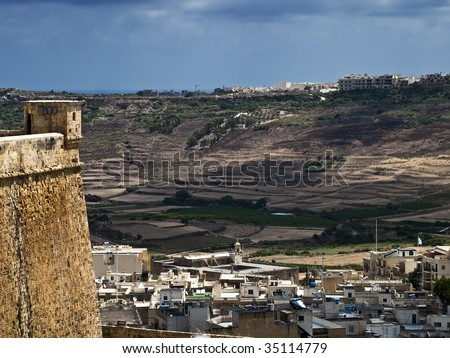 Bastion wall overlooking modern dwellings outside the citadel in Gozo - stock photo